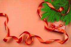 Flache Lage mit roter Geschenkbox, rotem Band und Weihnachtsbaumast auf rotem Hintergrund Stockfotos