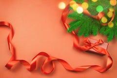 Flache Lage mit roter Geschenkbox und rotem Band, Weihnachtsbaumast und Weihnachtslichter bokeh auf rotem Hintergrund Lizenzfreies Stockbild