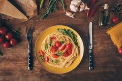 flache Lage mit traditionellen italienischen Teigwaren mit Tomaten und Arugula in der Platte auf Holztisch Stockfoto
