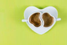 Flache Lage mit zwei Schalen Espresso auf grünem Brett Stockfoto