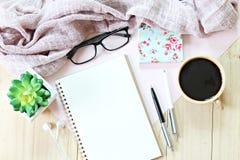 Flache Lage oder Draufsicht des gestrickten Schals, des offenen leeren Notizbuchpapiers, der Kaffeetasse und der Brillen auf hölz lizenzfreie stockfotografie