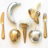Flache Lage Phot - Gold- und Silberäpfel, Bananen, Geschirr Stockbild