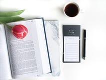 Flache Lage: Rote Tulpe, rote Blumenbl?tter und eine Bibel auf einer wei?en Tabelle stockbild