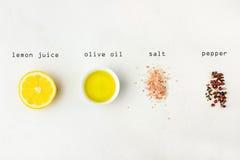 Flache Lage von Bestandteilen für Essigsoßesoße Zitrone, Olivenöl, roter schwarzer weißer Pfeffer des Himalajasalzes auf weißem S Lizenzfreie Stockfotos
