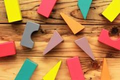 Flache Lage von hellen bunten hölzernen Zahlen zerstreute auf hölzerne hellbraune Planken, abstrakter Hintergrund Stockfotografie