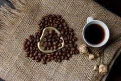 Flache Lage von Röstkaffeebohnen auf einer Tischdecke mit einem goldenen Herzen formte Untertasse und Kaffeetasse Schale Morgenes Stockbild