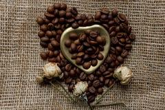 Flache Lage von Röstkaffeebohnen auf einer Tischdecke mit einem goldenen Herzen formte Untertasse und Kaffeetasse Schale Morgenes Stockbilder