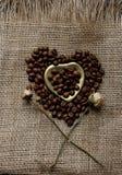 Flache Lage von Röstkaffeebohnen auf einer Tischdecke mit einem goldenen Herzen formte Untertasse und Kaffeetasse Schale Morgenes Lizenzfreie Stockbilder