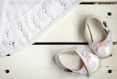 Flache Lage von reizenden weißen Weinleselackleder-Babyschuhen mit Rosabögen und stehende Spitze- und weißerhandgemachter gestric Stockfotografie