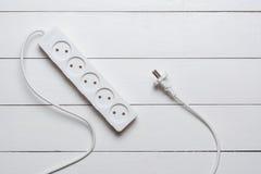 Flache Lage - weißes Verlängerungskabel auf Bretterboden lizenzfreie stockfotografie