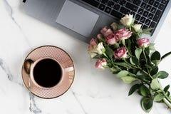 Flache Lage, weiblicher Schreibtisch des Draufsichtbürotischs Arbeitsplatz mit Laptop, Schale cofee und rosa Rosen des Blumenstra Stockbilder