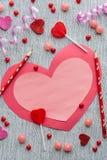 Flache Lageanordnung für rosa und roten Valentinsgruß mit Bleistiften und Süßigkeit auf grauem Hintergrund Lizenzfreie Stockbilder