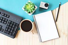 Flache Lageart des Büroarbeitsplatzschreibtisches mit leerem Notizbuchpapier, Computertastatur, Tasse Kaffee und Aktionskamera Stockfoto
