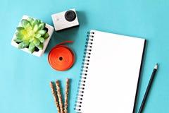 Flache Lageart des Büroarbeitsplatzschreibtisches mit leerem Notizbuchpapier, kleiner Aktionskamera und Zubehör auf blauem Hinter Stockfoto