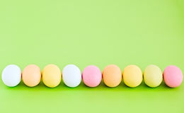 Flache Lagereihe von bunten Eiern auf einem Grünhintergrund Lizenzfreie Stockfotos