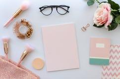 Flache Lagerosazusammensetzung mit leeren Anmerkungskosmetik, Make-upwerkzeugen, Gläser und stieg auf weißen Hintergrund Schönhei Stockfotos