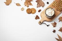 Flache Lagezusammensetzung mit heißem gemütlichem Getränk und Herbstlaub auf weißem Hintergrund stockfotografie