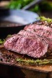Flache Schärfentiefe Saftige mittlere Rib Eye-Steakscheiben auf hölzernem Brett mit Gabel- und Messerkrautgewürzen und -salz lizenzfreies stockfoto