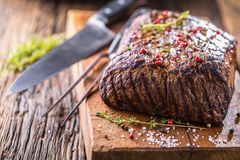 Flache Schärfentiefe Saftiges Rib Eye-Steak in der Wanne auf hölzernem Brett mit Kraut und Pfeffer Lizenzfreies Stockfoto