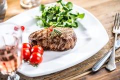 Flache Schärfentiefe Saftiges Rindfleischsteak Feinschmeckerisches Steak mit Gemüse und Glas rosafarbenem Wein auf Holztisch stockbild