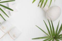 Flacher Draufsicht-Badekurorthintergrund der Lage: thailändische Massagetasche, -tücher und -palmblätter auf weißem Hintergrund G lizenzfreie stockbilder