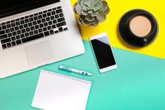 Flacher gelegter Entwurf des Arbeitsschreibtisches mit labtop Notizbuch, Smartphone und Kaktus auf grünem und gelbem Hintergrund stockfotos
