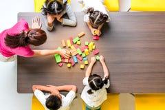 Flacher gelegter Schuss des asiatischen Lehrers spielen bunte Gestaltblöcke spielen mit asiatischem Studenten zusammen, Konzept f lizenzfreies stockfoto