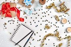 Flacher gelegter Weihnachts-oder Partei-Hintergrund mit farbigen Bändern, Dekorationen, Konfettis und Packpapier Notizblock für T stockfoto