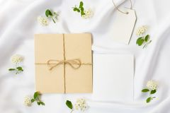 Flacher Lagearbeitsplatz, Modell Hochzeitseinladungskarten, Handwerksumschläge, weiße Blumen, Grünblätter und Spitze auf Weiß Stockfotos