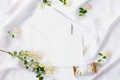 Flacher Lagearbeitsplatz, Modell Hochzeitseinladungskarten, Handwerksumschläge, weiße Blumen, Grünblätter und Spitze auf Weiß Lizenzfreie Stockfotografie