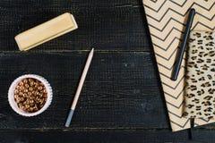 Flacher Lageausgangsschreibtisch Weiblicher Arbeitsplatz mit goldenen Zus?tzen, Tagebuch auf schwarzem Hintergrund stockfotos