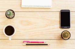 Flacher Lageschreibtisch mit Notizbüchern, intelligentem Telefon, Stift und einer Schale O lizenzfreie stockfotografie