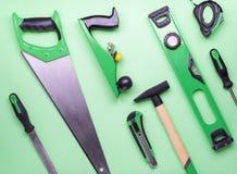 Flacher Plan: ein Satz Handwerkzeuge für Bau und Reparatur auf einem grünen Hintergrund stockfotografie