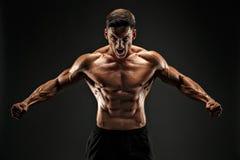 Flacher Unfall Mann der Eignung mit Muskeln auf dunklem Hintergrund Brüllen für Motivation lizenzfreies stockfoto