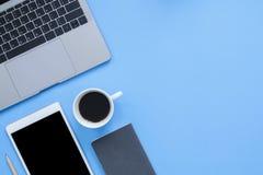 Flaches Draufsicht-Modellfoto der Lage des Funktionsraumes mit Laptop, Smartphone, dem Kaffee hoch und Notizbuch auf blauem Paste stockfotos