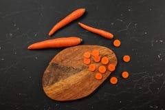 Flaches gelegtes Foto, Karotten einiges geschnitten zu den kleinen Kreisen auf Schneidebrett stockfotografie