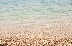 Flaches hellblaues Meer auf Schindelstrand Stockbilder