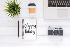 Flaches Lageansichtfoto des Arbeitsschreibtisches mit glücklichem Urlaubswunschnotizbuch, Kaffeetasse, Kamera und Laptop auf weiß lizenzfreie stockfotografie