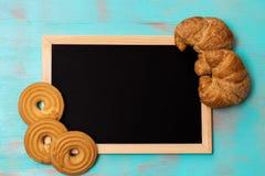 Flaches Lagedesign mit Butterplätzchen/Keksen, Hörnchen und gestalteter Tafel auf rustikalem Hintergrund des Knickentengrüns, mit stockfotografie