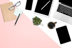Flaches Lagefoto des Bürotischs mit Laptop-Computer, digitaler Tablette, Handy und Zubehör auf dem modernem Weiß mit zwei Tönen u lizenzfreie abbildung