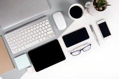 Flaches Lagefoto des Bürotischs mit Tastatur, Notizbuch, digitale Tablette, Handy, Bleistift, Brillen auf modernem Ton zwei Stockbilder