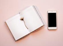 Flaches Lagefoto des rosa Arbeitsplatzschreibtisches mit Smartphone und Notizbuch Stockfotografie