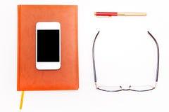 Flaches Lagefoto von Smartphone, von Notizblock, von Gläsern und von Stift Geschäft Stockfoto