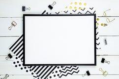 Flaches Lagemodell mit schwarzem Rahmen und Büroartikel auf weißem hölzernem Hintergrund Draufsichtmodell Blogschablone Stockbild