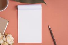 Flaches Lagenotizbuch und -rose gesetzt auf einen roten Schreibtisch Lizenzfreie Stockfotografie