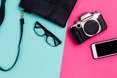 Flaches Lagereisendzubehör auf buntem blauem und rosa Hintergrund mit Smartphone, Gläsern, schwarzer Tasche und Kamera lizenzfreies stockfoto