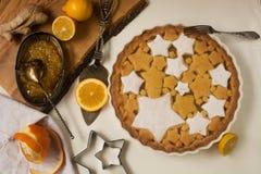 Flaches Lagetörtchen mit dem Zitronen-, Orangen- und Ingwerstau verziert mit sternförmigen Plätzchen Stockbild