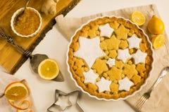Flaches Lagetörtchen mit dem Zitronen-, Orangen- und Ingwerstau verziert mit sternförmigen Plätzchen Stockfoto