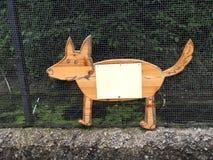 Flaches Zeichen der hölzernen Kontur des Hund (Fuchs) auf dem Metallnetz Lizenzfreies Stockfoto