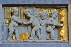 Flachrelief im Stein und im Gold von Engeln bei der Arbeit Stockfotos